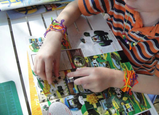 boy laying out glass beads onto magazine pictures