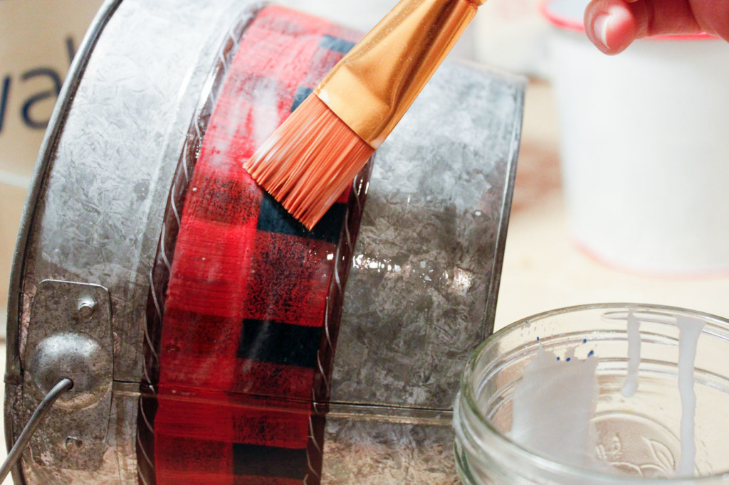 painting watered down glue onto pail