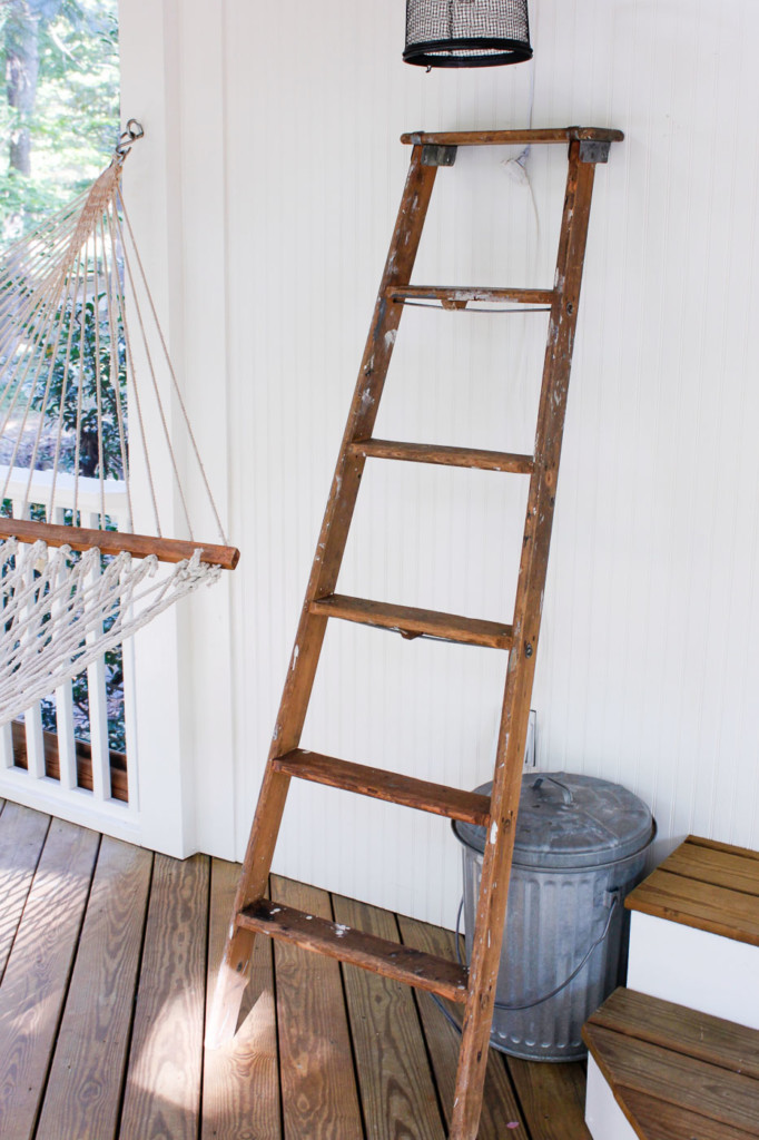 old ladder resting against white porch wall