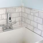 tiled and grouted marble subway tile backsplash around utility sink