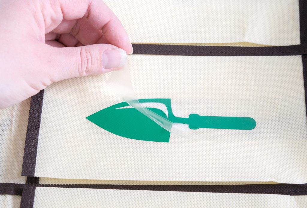You know your design is ironed onto the fabric well when the plastic peels up easily.