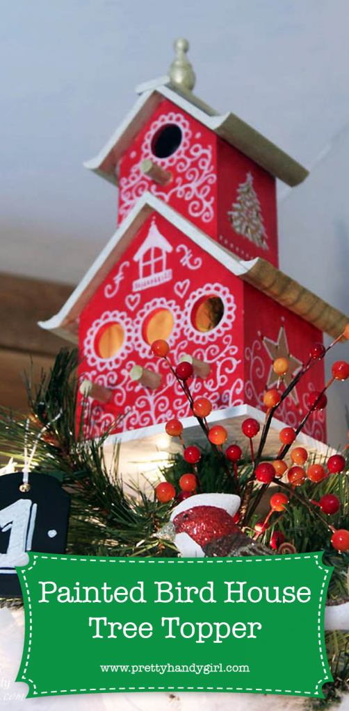 red bird house on top of christmas tree