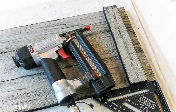 brad nail gun laying on top of assembled wood tray