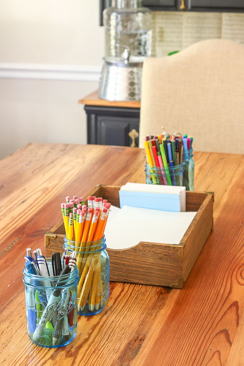 dining room table set with homework supplies pencils, paper, pens
