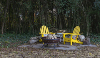 adirondack chairs around fire pit on old shed concrete pad
