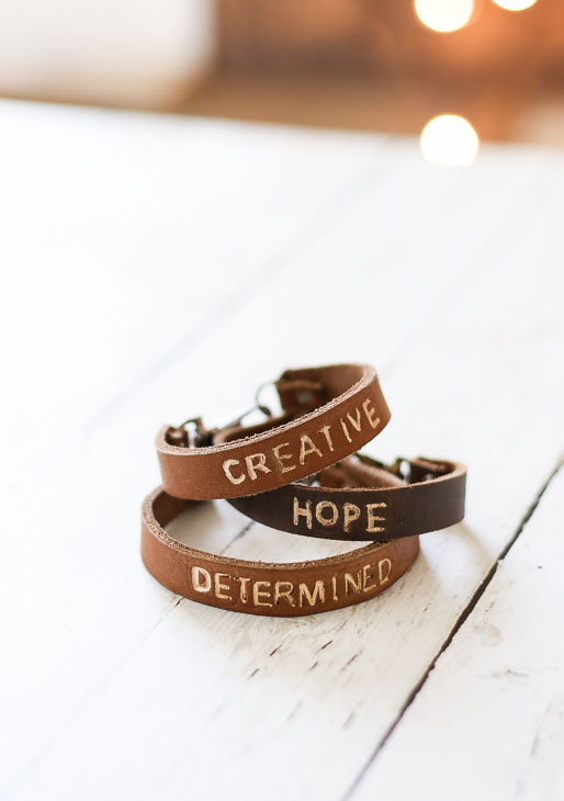 """golden tan and dark tan leather bracelets with """"creative"""", """"hope"""", and """"determined"""" stamped on them."""