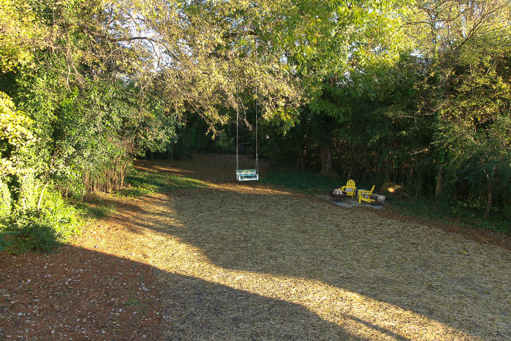 view from upstairs bedroom window of yard with tree swing and adirondack chairds