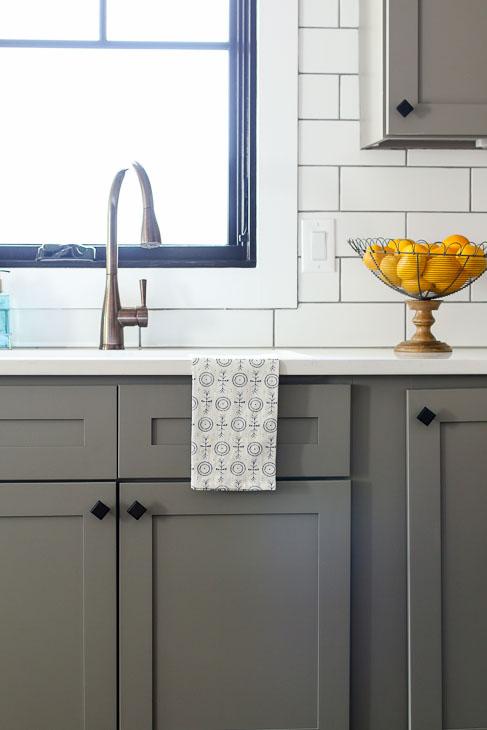 Plygem Mira black framed casement window over bronze faucet and gray cabinets