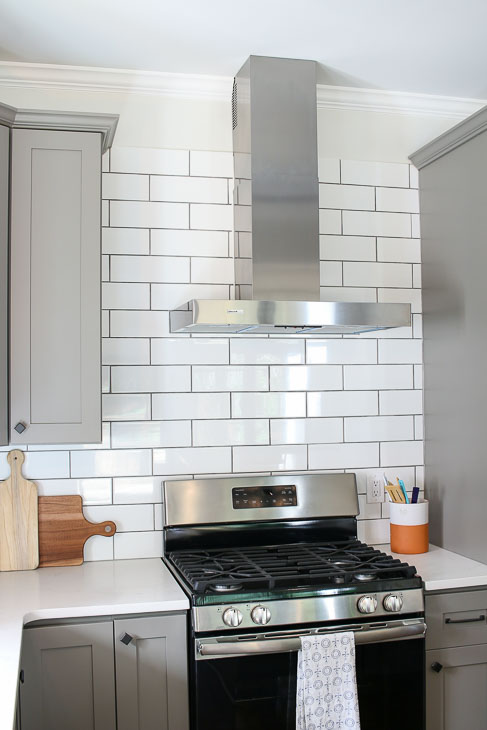 gray shaker cabinets with subway tile backsplash and stainless steel hood from Broan