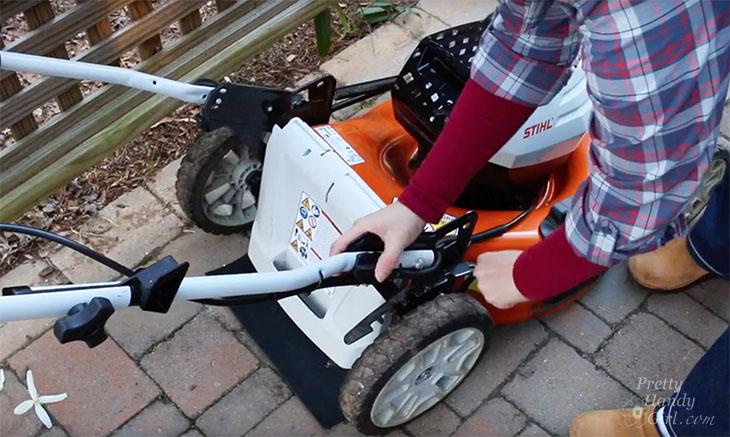 Adjusting mower height handle