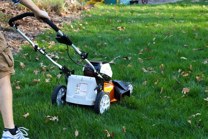 man pushing lawnmower shown from back