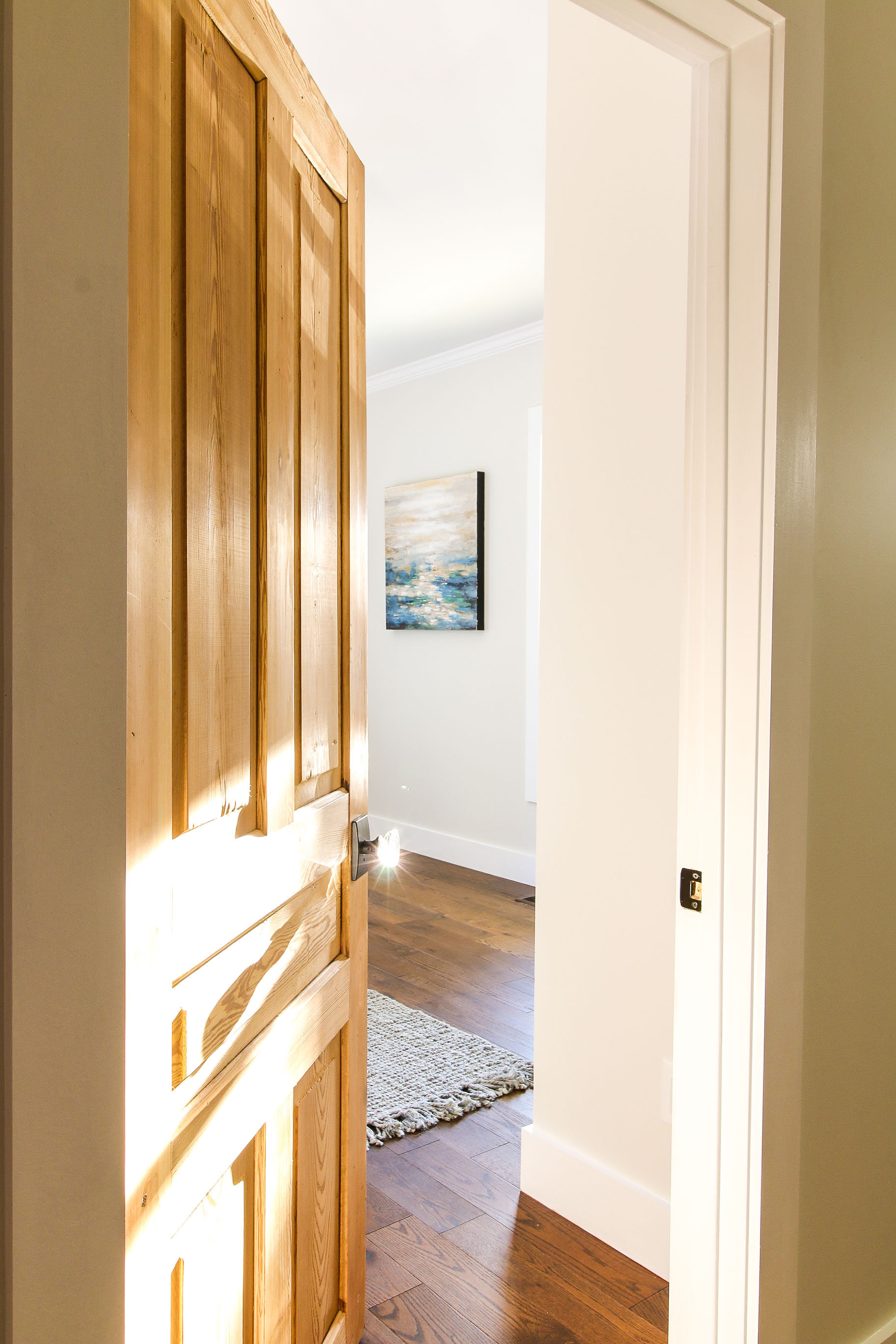 Door opening with ocean painting showing. Glass door knob with sun glinting on it.