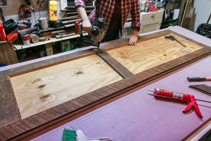 nail border pieces in place on reclaimed wood barn door