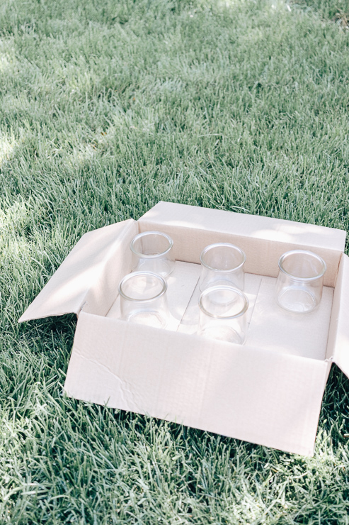 Place jars in a box to prepare for spray painting