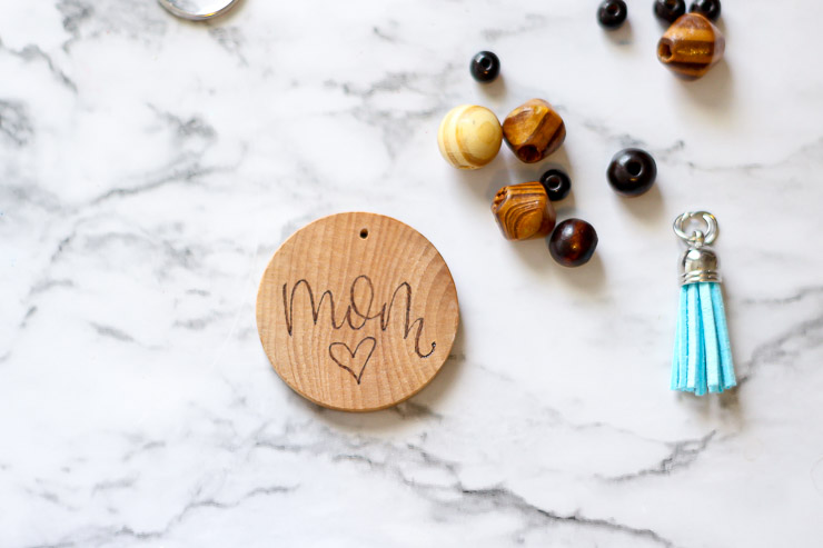 Personalized keychain assembly with a wood burned design