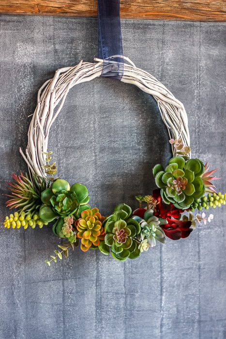 Finished DIY faux succulent wreath over chalkboard