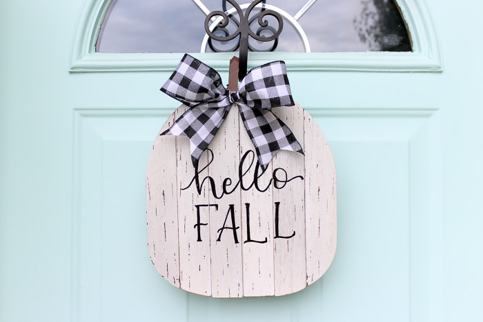 Finished hello fall pumpkin sign with buffalo check ribbon hanging on blue front door