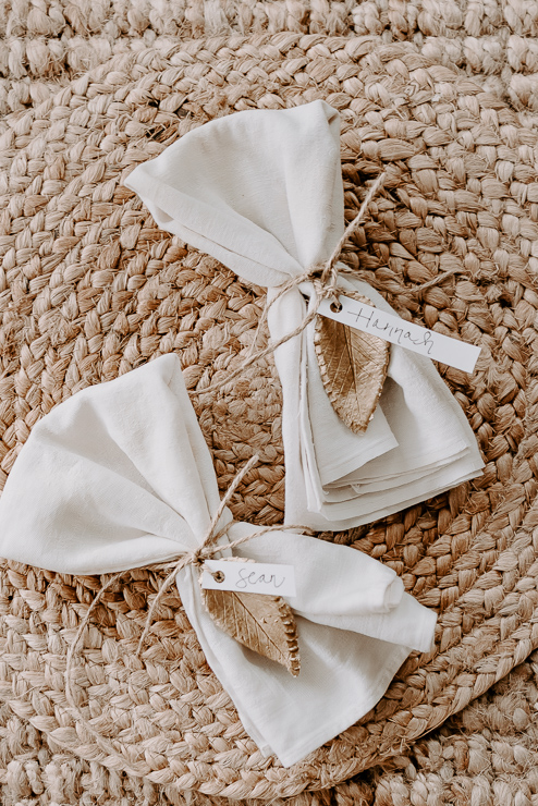 napkins tied with gold clay leaves and name tags