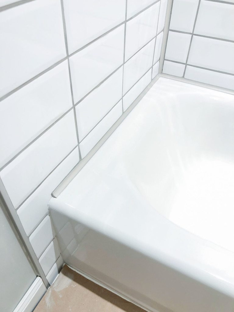 close up of schluter greige profiles around tub and along edge of tile