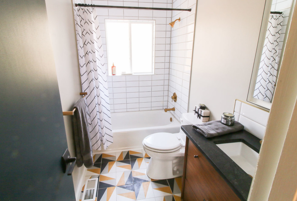 Millie's remodel bathroom, white stacked subway tile around white tub gold finishes and black and yellow houndstooth floor pattern
