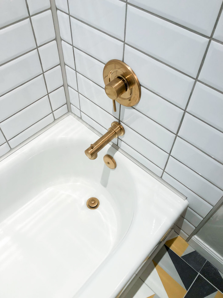 brushed gold moen tub spout and mixing valve in white tub and white tiles
